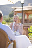 Smiling woman drinking hot chocolate on patio with whipped cream on nose Stock Photo