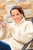 Smiling woman drinking hot cocoa relaxing garden Royalty Free Stock Photo