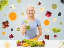 Smiling woman drinking juice or shake at home. Healthy eating, vegetarian food, diet, detox and people concept - smiling woman drinking green vegetable juice or Stock Images