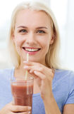 Smiling woman drinking juice or shake at home Stock Images