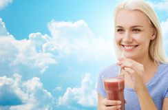 Smiling woman drinking juice or shake over sky Royalty Free Stock Photos