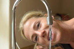 Smiling woman drinking from a kitchen faucet Stock Photo