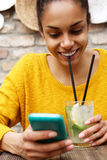 Smiling woman drinking mojito and using mobile phone at cafe Royalty Free Stock Photos