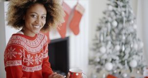 Smiling woman drinking a mug of Christmas coffee. Pretty smiling young African woman in a festive red sweater drinking a mug of Christmas coffee in front of the stock footage
