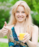 Smiling woman drinking orange juice Royalty Free Stock Image