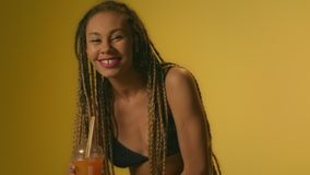 Smiling woman drinking orange juice and dancing in studio with yellow wall. stock footage