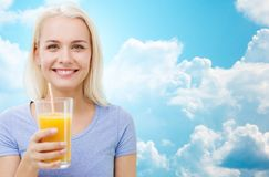 Smiling woman drinking orange juice Royalty Free Stock Images