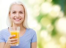 Smiling woman drinking orange juice stock photo