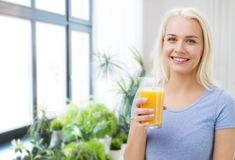 Smiling woman drinking orange juice at home royalty free stock photography