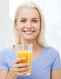 Smiling woman drinking orange juice at home Stock Photo
