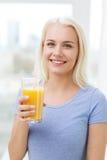Smiling woman drinking orange juice at home Stock Photo
