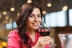 Smiling woman drinking red wine at restaurant. Leisure, drinks, degustation, people and holidays concept - smiling woman drinking red wine at restaurant Stock Photography