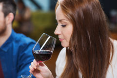 Smiling woman drinking red wine at restaurant. Leisure, drinks, degustation, people and holidays concept - smiling women drinking red wine at restaurant Stock Images