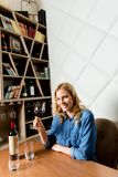 Smiling woman drinking red wine at restaurant stock photography