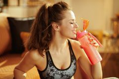 Smiling woman drinking from shaker with protein supplements royalty free stock photography