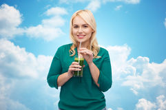 Smiling woman drinking vegetable juice or smoothie Royalty Free Stock Images