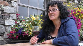 Smiling woman drinking wine at outdoors cafe stock video footage