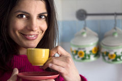 Smiling woman drinks a cup of coffee Stock Images