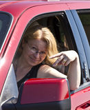 Smiling woman drives a red car Royalty Free Stock Images
