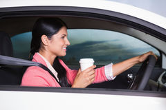 Smiling woman driving car while drinking coffee Royalty Free Stock Image