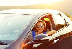 Smiling woman driving a car at sunset Stock Photography
