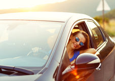 Smiling woman driving a car at sunset Royalty Free Stock Image