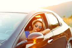 Smiling woman driving a car at sunset Royalty Free Stock Images