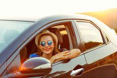 Smiling woman driving a car at sunset Royalty Free Stock Photo