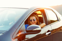 Smiling woman driving a car at sunset Stock Photo
