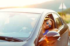 Smiling woman driving a car at sunset Stock Images