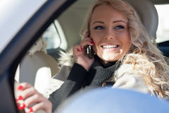 Smiling woman driving while phoning Royalty Free Stock Photos