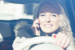 Smiling woman driving while phoning Royalty Free Stock Photo