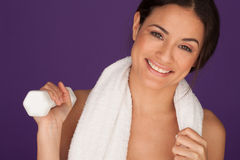 Smiling woman with a dumbbell. Smiling woman with a towel around her neck holding up a dumbbell in her hand during her fitness exercises Stock Photo