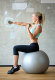 Smiling woman with dumbbells and exercise ball Royalty Free Stock Image