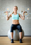 Smiling woman with dumbbells and exercise ball. Fitness, sport, training, future technology and lifestyle concept - smiling woman with dumbbells and exercise Royalty Free Stock Photos