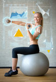 Smiling woman with dumbbells and exercise ball Royalty Free Stock Photography