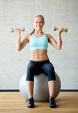 Smiling woman with dumbbells and exercise ball Royalty Free Stock Photo