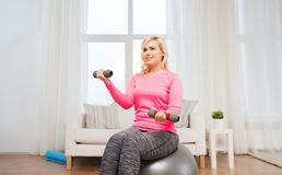 Smiling woman with dumbbells exercising at home Stock Image