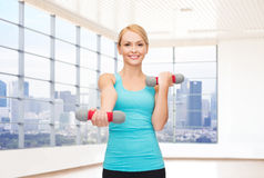 Smiling woman with dumbbells flexing biceps in gym Royalty Free Stock Photos