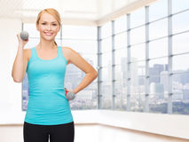 Smiling woman with dumbbells flexing biceps in gym Stock Images