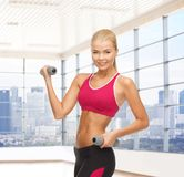 Smiling woman with dumbbells flexing biceps in gym Royalty Free Stock Photography