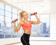 Smiling woman with dumbbells flexing biceps in gym Stock Photography
