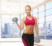 Smiling woman with dumbbells flexing biceps in gym. Fitness, sport, fitness and people concept - smiling woman with dumbbells flexing biceps over gym or home stock image