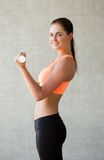 Smiling woman with dumbbells in gym Royalty Free Stock Images