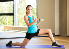 Smiling woman with dumbbells in gym Stock Photo