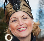 Smiling woman with earrings and a golden hat. Stock Image