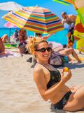 Smiling woman eat fruit on the beach stock photography