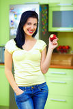 Smiling woman eating apple, kitchen interior Stock Images