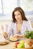 Smiling woman eating breakfast Stock Photo