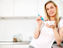 Smiling woman eating breakfast. Smiling young blonde woman standing in her kitchen eating a healthy breakfast of cereal topped with yoghurt and fresh berries Stock Photos